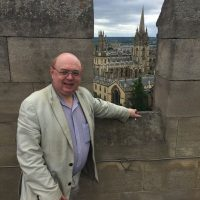 A picture of the author of the blog and book, David Bradbury. David is leaning on a wall overlooking a pretty cityscape