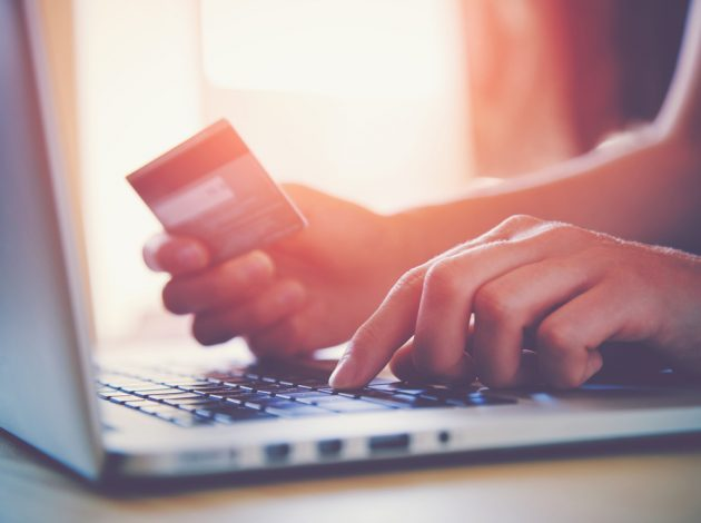 Image shows someone's hands holding a credit card over a laptop keyboard, like they are shopping online