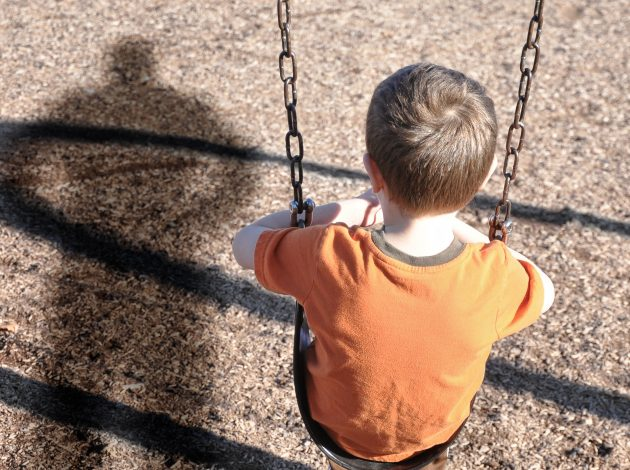 A young boy is sitting on a swing set and looking at a shadow figure of a man or bully at a playground
