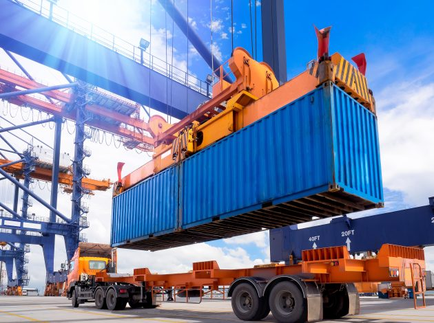 Image shows a shipping container being craned off a container lorry, indicative of trade